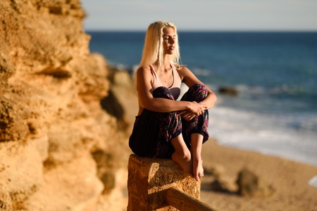 Woman enjoying the sunset on a beautiful beach in Cadiz, Andalusia, Spain. Young female sitting on beautiful stairs looking at the sea with golden light. Stock Photo