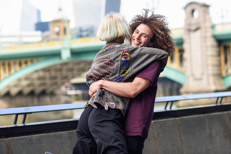 Happy couple hugging near the Southwark bridge over River Thames, London