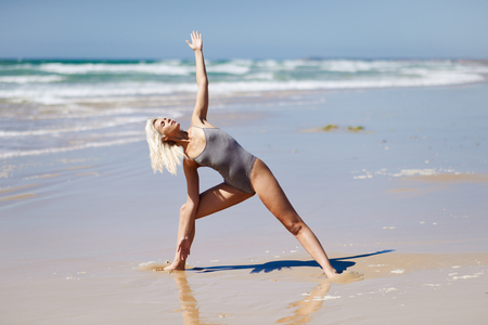 Caucasian blonde woman practicing yoga in the beach 写真素材 - 123424858