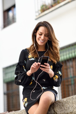 Woman listening to the music with earphones and smart phone outdoors. Banque d'images