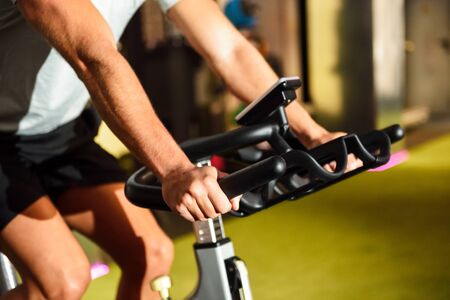 Hands of a man training at a gym doing cyclo indoor. Reklamní fotografie