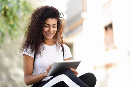 Young black woman in sportswear using digital tablet outdoors Stock Photo