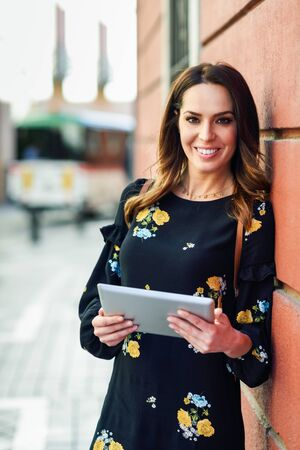 Smiling young woman using digital tablet outdoors.