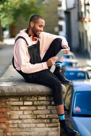 Young black man using digital tablet in urban background.