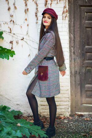Giovane bella donna con capelli molto lunghi che indossa cappotto invernale e berretto in foglie d'autunno sfondo Archivio Fotografico