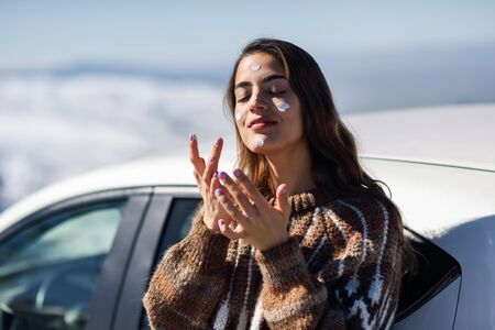Young woman applying sunscreen on her face in snow landscape Foto de archivo
