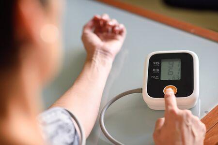 Mujer midiendo su propia presión arterial en casa. Foto de archivo