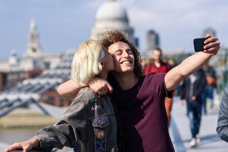 Happy couple taking a selfie photograph on Londons Millennium Bridge