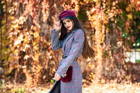 Young beautiful girl wearing winter coat and cap in autumn leaves background. 写真素材
