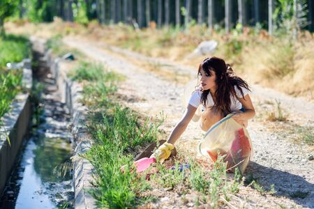 Woman hand collecting garbage of the grass in the countryside 写真素材