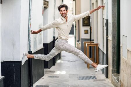 Young happy man jumping in the street.