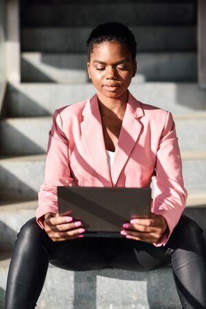 Black businesswoman sitting on urban steps working with a laptop computer.
