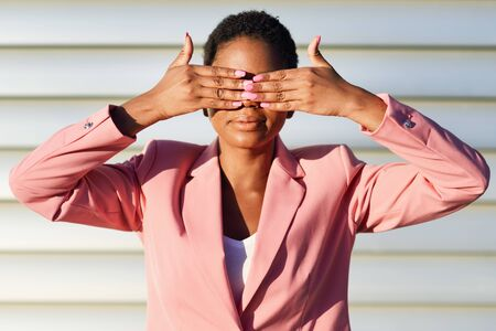 Funny black woman standing on urban wall covering her eyes with her hands.