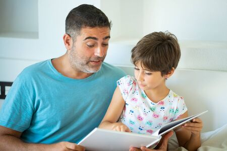 Middle-age father with her eight years daughter using digital tablet in bedroom.