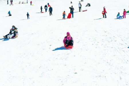 People coming down on sleds at Sierra Nevada ski resort.
