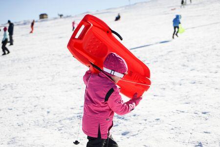 Little girl sledding at Sierra Nevada ski resort. Stok Fotoğraf