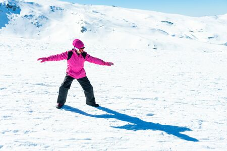 Little girl playing snowboard trainer on snow 写真素材
