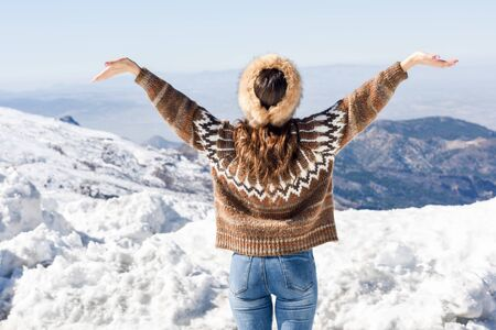 Young woman enjoying the snowy mountains in winter 写真素材
