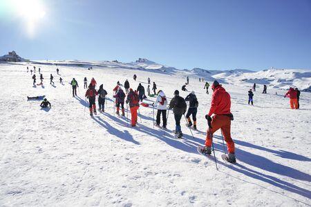 Group of people hiking with snowshoes at Sierra Nevada ski resort. Sajtókép