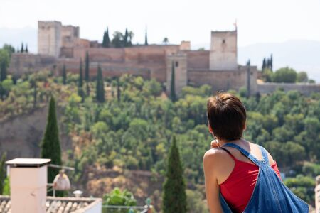 Rear view of woman looking at the Alhambra of Granada. Stock Photo