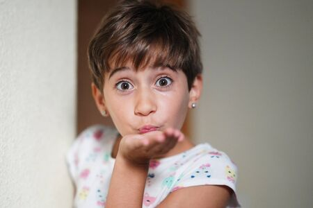Funny little girl, eight years old, blowing a kiss