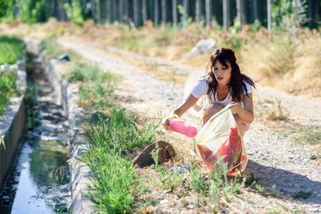 Woman hand collecting garbage of the grass in the countryside Imagens