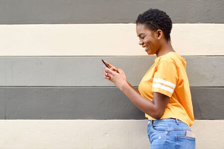 Young black woman laughing using her smart phone outdoors Reklamní fotografie