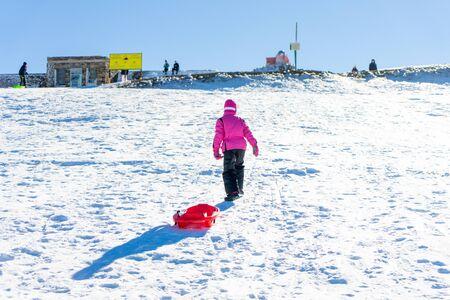 Little girl sledding at Sierra Nevada ski resort. Stock fotó