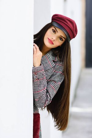Beautiful girl with very long hair wearing winter coat and cap outdoors.