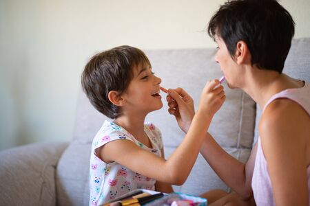 Mother and her little daughter doing make up for each other Stock Photo