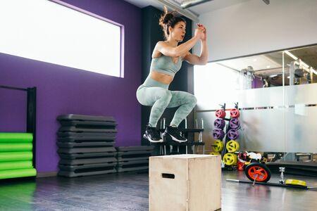 Caucasian female doing box jump workout at gym. Stok Fotoğraf