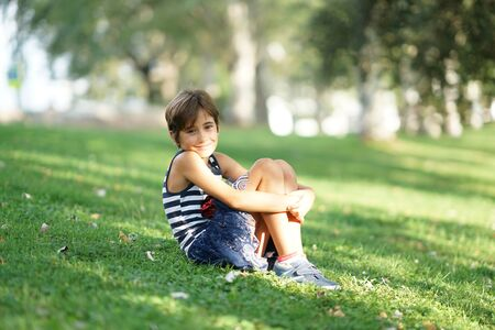 Little girl, eight years old, sitting on the grass outdoors.