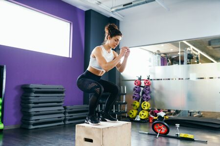 Athletic woman doing squats on box at the gym Stok Fotoğraf