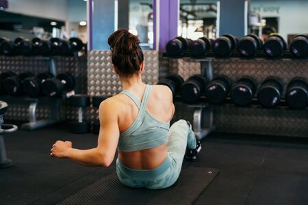 Young sportswoman wearing sportswear, on yoga mat doing situps in gym. Fitness woman doing abs crunches. Banco de Imagens