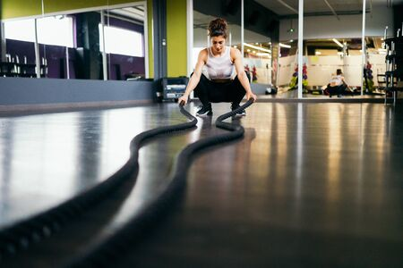 Young and athletic woman using training ropes in a gym.