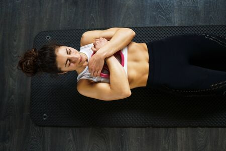 Young sportswoman on yoga mat doing situps in gym. Banco de Imagens