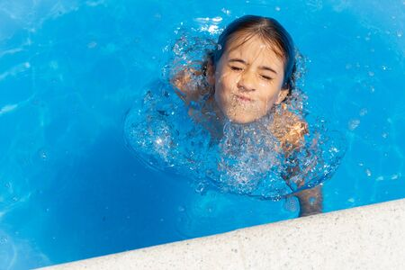 Cute girl eight years old playing in a swimming pool.