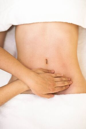 Top view of hands massaging female abdomen.Therapist applying pressure on belly