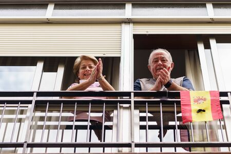 Older couple clapping in the window in support of people against the coronavirus 스톡 콘텐츠
