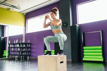 Fitness woman jumping onto a box as part of exercise routine.