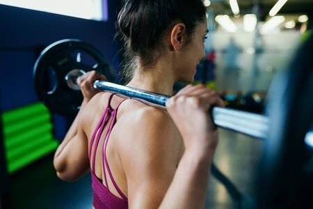 Athletic woman in gym lifting weights at the gym Фото со стока