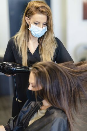 Hairdresser drying her clients hair with a hairdryer wearing protective masks in a beauty centre.