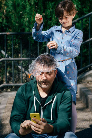 Girl blowing up a water-filled balloon over her fathers head