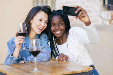 Two friends making a selfie sitting at a table outside a bar while drinking a glass of red wine.
