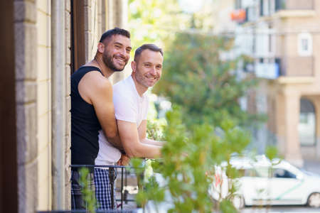 Gay couple in a romantic moment leaning out of their balcony.