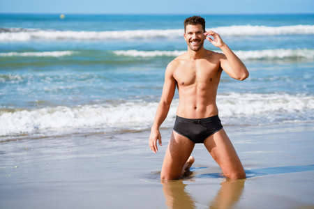Handsome man on his knees smiling on the sand of the beach