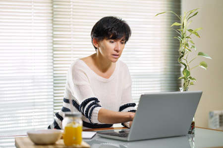 Woman teleworking from home with her laptop. Imagens