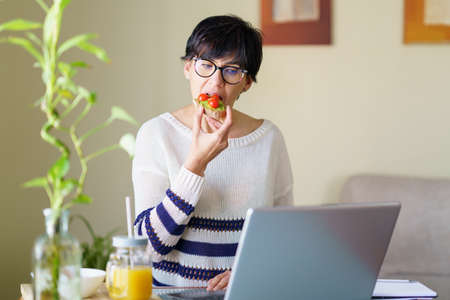 Woman eating some healthy food, while teleworking from home on her laptop. Imagens
