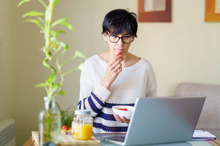 Woman eating strawberries while teleworking from home on her laptop Imagens