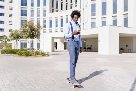 Black businessman on a skateboard looking at his smartphone outdoors.